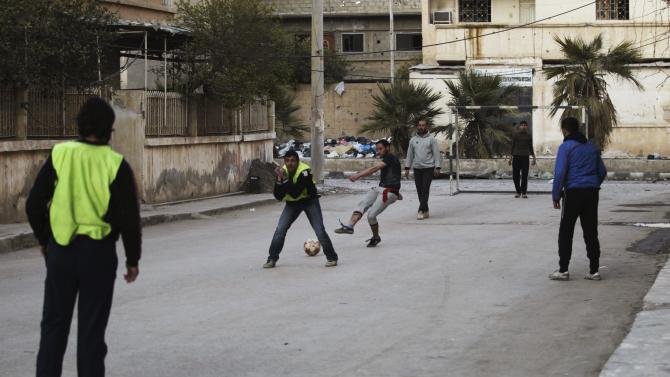 Activists and Free Syrian Army fighters play soccer along a street in Deir al-Zor