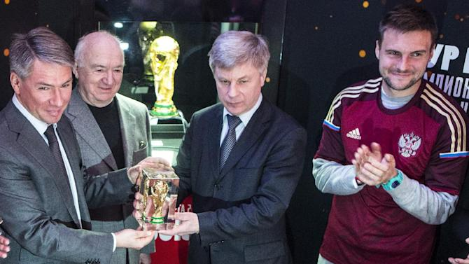 From left: Alexei Sorokin, CEO of the 2018 FIFA World Cup in Russia, Nikita Simonyan vice-president of the Russian Football Union, Nikolai Tolstykh, famous Russian football player and president of the Russian Football Union and Vladimir Granat, player for the Russian national team, attend a presentation of FIFA World Cup, seen in the background, in Moscow, Russia, Monday, March, 24, 2014