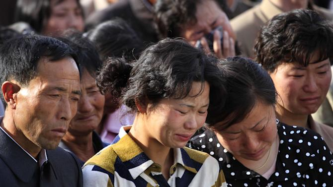 """In this Saturday, May 17, 2014 photo, families of victims of an accident at an apartment construction site in Pyongyang, North Korea grieve during a gathering in the capital where senior officials apologized and took responsibility. The word of the collapse in the secretive nation's capital was reported Sunday morning by the North's official Korean Central News Agency, which gave no death toll but said that the accident was """"serious"""" and upset North Korea's leader, Kim Jong Un. (AP Photo/Jon Chol Jin)"""