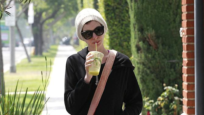 Anne Hathaway pets her seemingly pregnant friend's belly as the two have breakfast together in LA