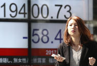 A woman walks past an electronic stock indicator of a securities firm in Tokyo, Tuesday, Feb. 14, 2017. Shares in Asia fell back after an early rally on Tuesday, as investors awaited comments to Congress by Federal Reserve chair Janet Yellen. (AP Photo/Shizuo Kambayashi)