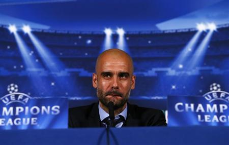 Bayern Munich's head coach Pep Guardiola attends a news conference at a hotel in London, England February 18, 2014. REUTERS/Eddie Keogh