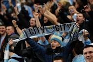 Manchester City fans celebrate after a match in April 2012. English Premier League clubs have been warned to bring their spending under control, after a new review into football finances showed that players' wages were at record levels, outstripping growth in club revenues