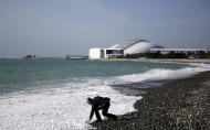 A beachgoer reaches down to touch the Black Sea as Fisht Olympic Stadium stands in the background, home of tonight's 2014 Winter Olympics closing ceremony, Sunday, Feb. 23, 2014, in Sochi, Russia. (AP Photo/David Goldman)