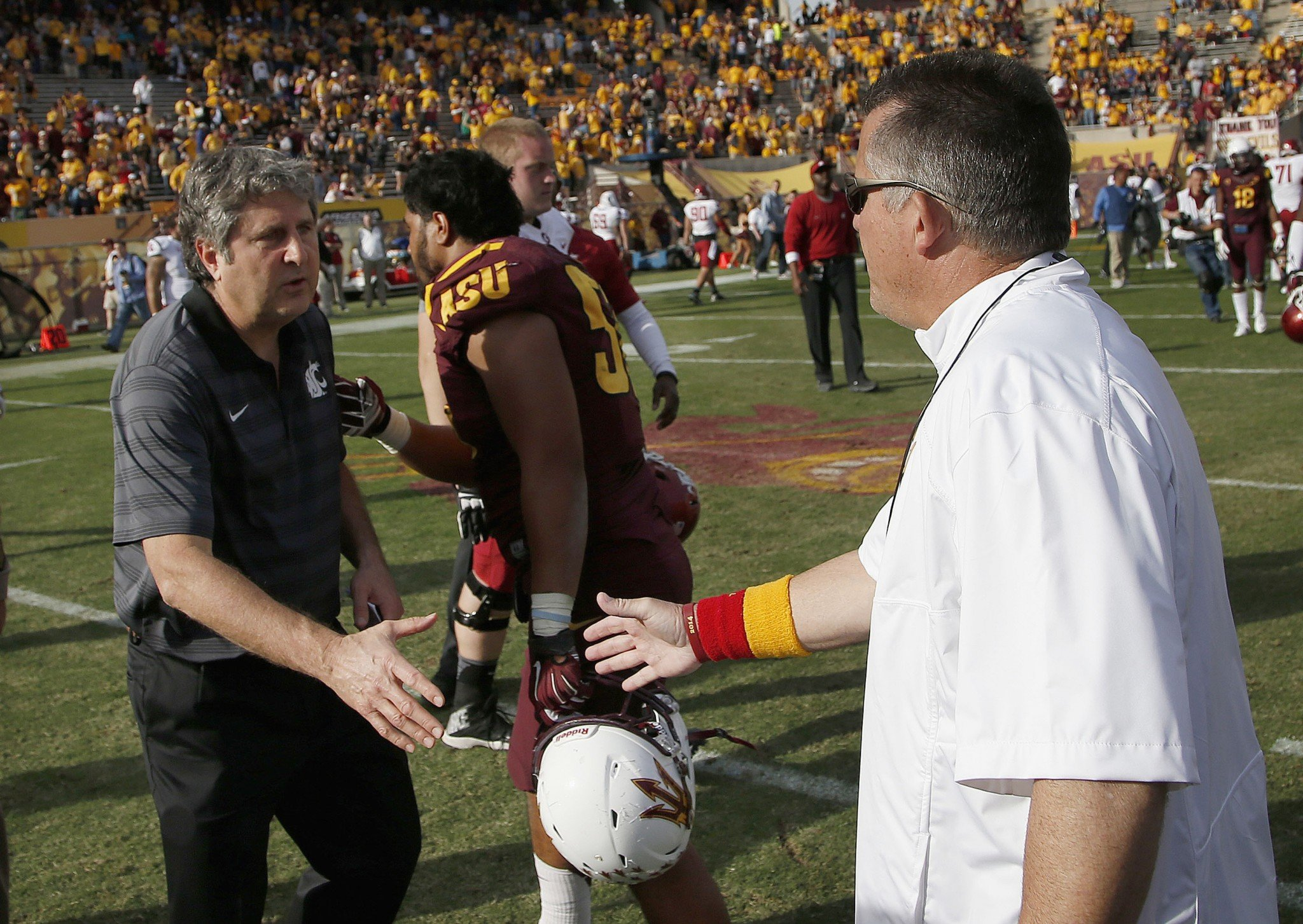 Things were a bit more cordial between Mike Leach and Todd Graham back in 2014, when this photo was taken. (AP Photo/Ross D. Franklin)