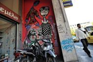 A man walks past graffiti related to the economic crisis in central Athens. The leaders of the eurozone's four biggest economies on Friday vowed measures to boost growth in the face of a relentless debt crisis, including an injection of up to 130 billion euros ($163 billion)