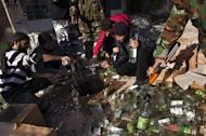 Syrian rebels empty bottles of alcohol in a drain in the Masakin Hanano district of the northern city of Aleppo on December 28, 2012. Syrian troops bombarded rebel bastions near the capital on Sunday a day after at least 32 civilians including 11 children were killed by air strikes and artillery fire in the Damascus area, a watchdog said