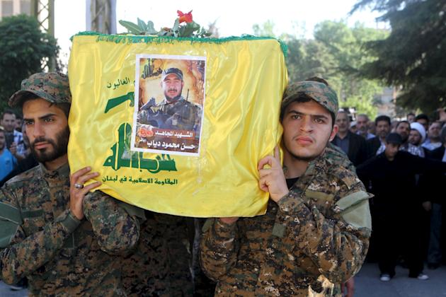 Lebanon's Hezbollah members carry the coffin of their fellow fighter Mahmoud during his funeral in Baalbek