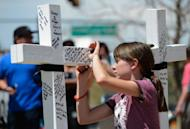 Emma Brazelton, 11, writes a personal note on a white wood cross with the name of each victim who was killed during the last weekend's mass shooting at Century 16 movie theater, in Aurora, Colorado