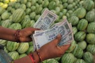 A farmer counts money at a fruit market in India. The Indian rupee plumbed new depths on Friday, sinking to a record low against the dollar for the third successive day amid turmoil on global markets