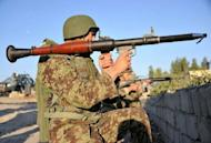 An Afghan National Army (ANA) soldier holds a rocket-propelled grenade launcher as he keeps watch near the scene of a suicide attack in Jalalabad on December 2. Taliban insurgents launched a major suicide attack against a NATO base at an Afghan city airport, killing five people and wounding several foreign troops, officials said