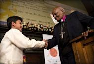 """South African Archbishop Desmond Tutu (R) shakes hands with Cris """"Kesz"""" Valdez, 13, after awarding him with the Children's Peace Prize at the Ridderzaal in the Hague. Valdez was chosen for the work of his """"Championing Community Children"""" charity which raises funds to hand out gift parcels to needy children in Cavite City, about 30 kilometres (18 miles) south of the capital Manila"""