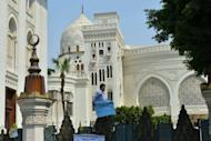 An Egyptian protester stands on the gate of the presidential palace during a demonstration in Cairo onlast week by people wanting to air grievances directly with President Mohamed Morsi. Instead of being sworn in before parliament, Morsi took the presidential oath before the constitutional court
