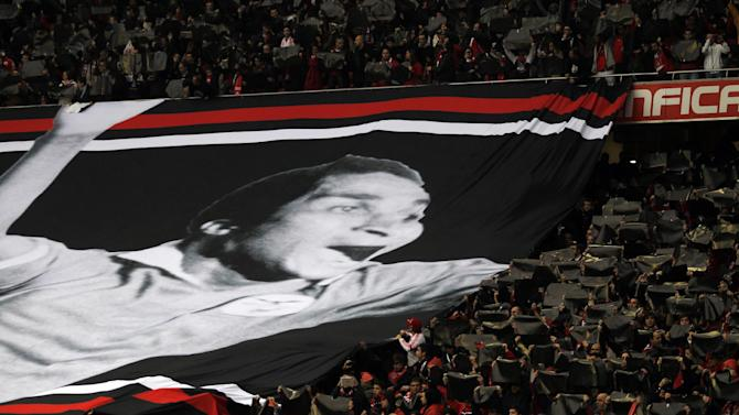 Benfica supporters hold black sheets beside a giant banner with the image of Benfica's player icon Eusebio during a tribute to him prior the Portuguese league soccer match between Benfica and Porto at Benfica's Luz stadium in Lisbon, Sunday, Jan. 12, 2014.  Eusebio died on Jan. 5 aged 71