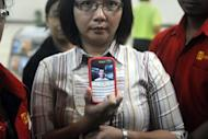 Yanny Meriana shows a photograph of family friend Edward Pangabean, who was a passenger on the ill-fated Russian Sukhoi Superjet 100, at the arrival area of Halim airport in Jakarta. A Russian Sukhoi Superjet 100 with about 50 people on board went missing in a mountainous area south of the Indonesian capital Jakarta during a demonstration flight Wednesday, officials said