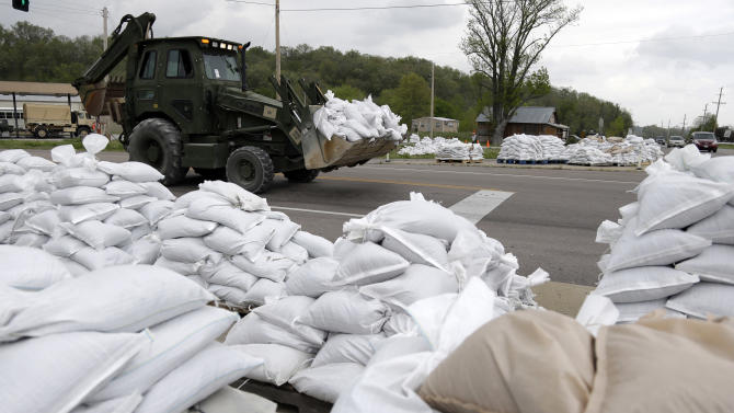 Heavy machinery moves sandbags as other sit staged, ready for possible use in the fight against floodwaters Tuesday, April 23, 2013, in Dutchtown, Mo. The tiny community of Dutchtown is doing what it can to prepare ahead of any possible flood. (AP Photo/Jeff Roberson)
