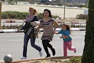 Israelis run towards a shelter in Nitzan, south of the coastal city of Ashdod during a rocket attack from the nearby Palestinian Gaza Strip. New Israeli air strikes on the Gaza killed three Palestinians on Sunday, raising the death toll in a latest round of violence to 18, as militants fired over 120 rockets into Israel