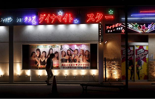 A man walks outside a club with an advertisement depicting women from the Philippines in the red light district in Ota