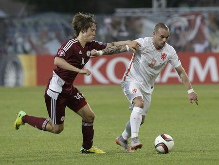Latvia's Ikaunieks runs for the ball with Netherlands' Sneijder during their soccer Euro 2016 qualification match in Skonto stadium in Riga