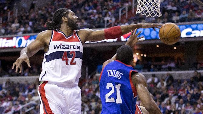 Washington Wizards power forward Nene (42), blocks a shot by Philadelphia 76ers forward Thaddeus Young (21) during the first half of an NBA basketball game on Monday, Jan. 20, 2014 in Washington