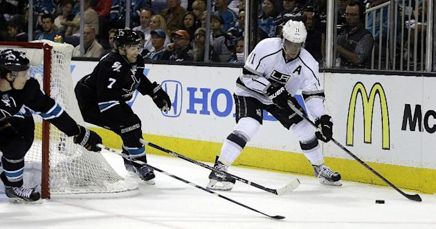 Los Angeles Kings' Anze Kopitar, right, moves the puck past San Jose Sharks' Brad Stuart (7) during the first period of Game 1 of an NHL hockey first-round playoff series Thursday, April 17, 2