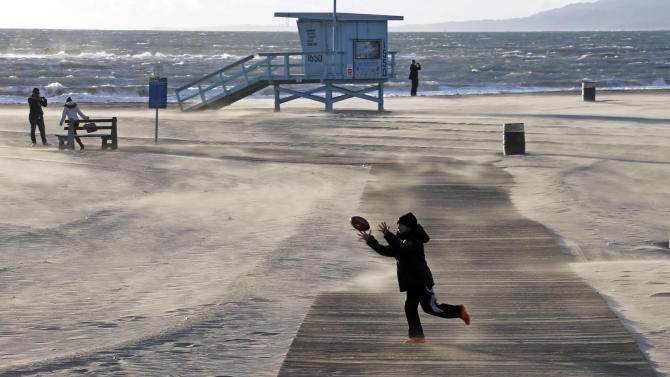 Bundled up against the elements, a boy catches a football as frigid, gusting winds blow sand in drifts across a boardwalk on a nearly-deserted beach near the pier at Santa Monica, Calif., Thursday, Jan. 10, 2013.  Strawberry growers are covering their crops while San Diego zookeepers are turning on heaters for the chimpanzees as Southern California braces for a cold snap expected to drop temperatures to a six-year low.  (AP Photo/Reed Saxon)