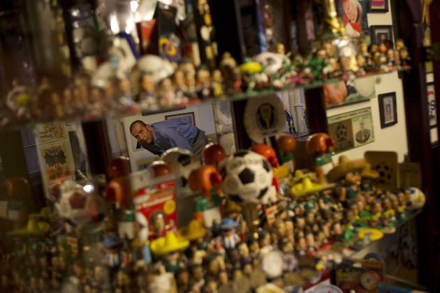 In this April 22, 2014 photo, Francisco Forastiere is reflected as he peers into a curio cabinet containing figurines of soccer players and World Cup mascots, in Mexico City. The former sports announc