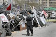 A man passes by the pro-Russian activist barricades at a regional administration building that they had seized earlier in Donetsk, Ukraine, Tuesday, April 15, 2014. Several government buildings have fallen to mobs of Moscow loyalists in recent days as unrest spreads across the east of the country. (AP Photo/Efrem Lukatsky)