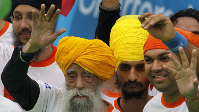Centenarian marathon runner Fauja Singh, 101, left, originally from Beas Pind, in Jalandhar, India but who now lives in London, waves after finishing a 10-kilometer race, held as part of the annual Hong Kong Marathon, in Hong Kong Sunday, Feb. 24, 2013. Singh will retire from public racing after competing in the marathon. (AP Photo/Vincent Yu)