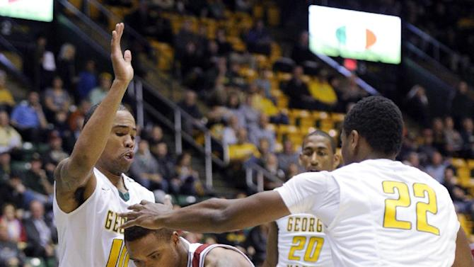 Massachusetts guard Derrick Gordon (2) fights for the ball against George Mason guard Sherrod Wright (10), Marquise Moore (22) and Jalen Jenkins (20) during the first half of an NCAA college basketball game, Wednesday, Jan. 15, 2014, in Fairfax, Va