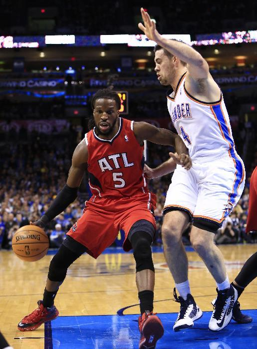 Atlanta Hawks forward DeMarre Carroll (5) drives to the basket around Oklahoma City Thunder power forward Nick Collison, right, during the first quarter of an NBA basketball game, Monday, Jan. 27, 2014, in Oklahoma City