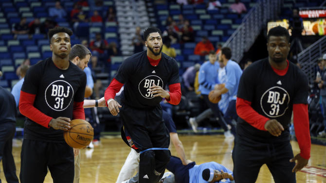 New Orleans Pelicans forward Anthony Davis, center, guard Buddy Hield, left, and forward Solomon Hill, warm up before of an NBA basketball game against the Denver Nuggets in New Orleans, Wednesday, Oct. 26, 2016. The t-shirts honor former teammate Bryce Dejean-Jones, who was killed during the off season. (AP Photo/Gerald Herbert)