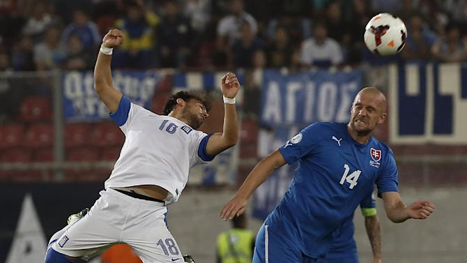 Greece's Lazaros Christodoulopoulos, left,  fights for the ball with Slovakia's Martin Jacubo  during their World Cup Group G qualifying soccer match at the Karaiskaki stadium in the port of Piraeus, near Athens, Friday, Oct. 11, 2013