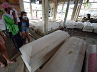 Bereaved Philippinos try to find dead relatives among coffins set out for victims of Typhoon Bopha, in New Bataan, Compostela Valley. The typhoon that has killed hundreds of people and wreaked devastation in the Philippines is set to smash into the country again Sunday, forecasters warn