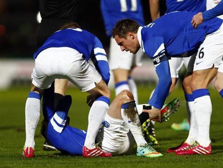 Everton's Jagielka holds the leg of team mate Oviedo as he lies with a broken leg during their English FA Cup soccer match against Stevenage in Stevenage