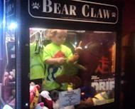 In this April 14, 2014 photo provided by Rachelle Hildreth, a 3-year-old boy plays with stuffed toys inside a claw crane game machine at a bowling alley in Lincoln, Neb. Police say a 24-year-old woman called 911 Monday afternoon because son was missing from her apartment. Authorities say the toddler was reunited, unharmed, with his mother after employees found him inside the coin-operated game. (AP Photo/Courtesy Rachell Hildreth)