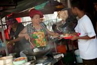 Soon Chuan Choo (C) passing char kway teow to a customer in Georgetown, the state of Penang's capital city.