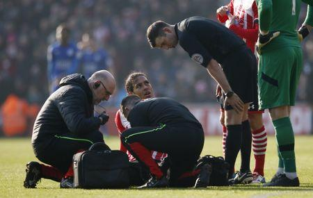 Southampton's Virgil van Dijk receives medical attention as referee Michael Oliver looks on