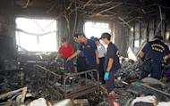 Police and firemen inspect a badly damaged room following a fire at Sinying Hospital near the southern Taiwanese city of Tainan. A blaze tore through a Taiwan hospital for bed-bound seniors and mentally ill patients Tuesday, killing 12 and injuring 60, with police reportedly arresting a patient suspected of starting the fire