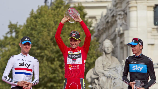 Geox-TMC team member Juan Cobo, center, celebrates on the podium after winning the Spanish Vuelta cycling race with second placed Sky Procycling rider Christopher Froome from UK, left, and third placed Sky Procycling rider Bradley Wiggins from UK, right, in Madrid, Spain, Sunday, Sept. 11, 2011. (AP Photo/Arturo Rodriguez)