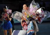 Ladies winner Japan's Mao Asada (R) receives flowers and presents from supporters during the awarding ceremony of the Four Continents figure skating championships in Osaka on February 10, 2013