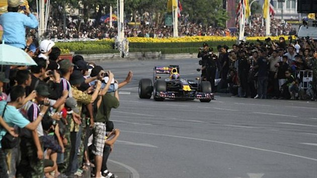 A Red Bull Formula One race car drives on Rajdamnoen Avenue, as part of the celebrations for Thailand's King Bhumibol Adulyadej's 83rd birthday, in Bangkok (Reuters)