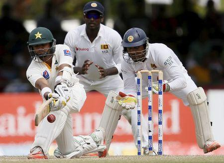 Pakistan's Ali plays a shot next to Sri Lanka's Chandimal and captain Angelo Mathews during the fourth day of their second test cricket match in Colombo