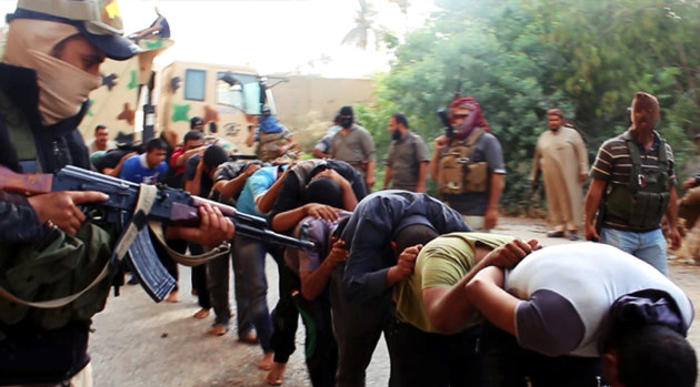 FILE - This file image posted on a militant website on Saturday, June 14, 2014, which has been verified and is consistent with other AP reporting, appears to show militants from the al-Qaida-inspired Islamic State of Iraq and the Levant (ISIL) leading away captured Iraqi soldiers dressed in plain clothes after taking over a base in Tikrit, Iraq. Human Rights Watch released a report Friday, June 27, 2014 that based on analysis of the photos and satellite imagery, the militants killed between 160 to 190 men in two locations in Tikrit between June 11 and June 14.(AP Photo via militant website, File)