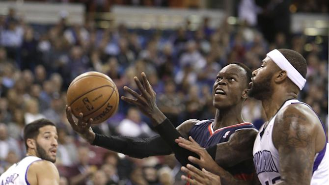 Atlanta Hawks guard Dennis Schroder, of Germany, center, drives to the basket against Sacramento Kings center DeMarcus Cousins, right, during the first quarter of an NBA basketball game in Sacramento, Calif., Tuesday, Nov. 5, 2013