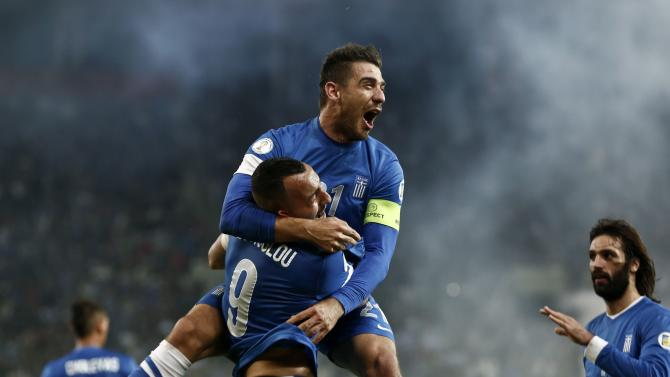 Greece's Kostas Katsouranis jumps onto Kostas Mitroglou as they celebrate Mitroglou's goal against Romania during their 2014 World Cup qualifying playoff first leg soccer match at Karaiskaki stadium in Piraeus