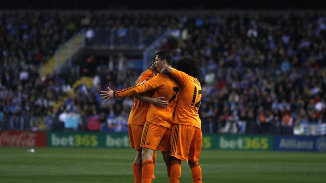Real Madrid's Cristiano Ronaldo is congratulated by his team mates after scoring a goal against Malaga during their Spanish First Division match in Malaga