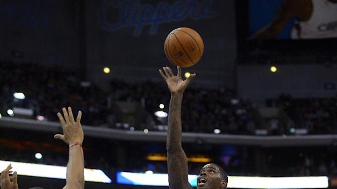 Utah Jazz forward Marvin Williams, right, shoots as Los Angeles Clippers center Ryan Hollins defends during the first half of an NBA basketball game on Saturday, Feb. 1, 2014, in Los Angeles