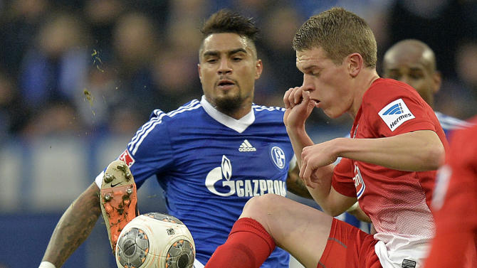 Schalke's Kevin-Prince Boateng, left, and Freiburg's Matthias Ginter challenge for the ball during the German Bundesliga soccer match between FC Schalke 04 and SC Freiburg in Gelsenkirchen, Germany, Sunday, Dec. 15, 2013