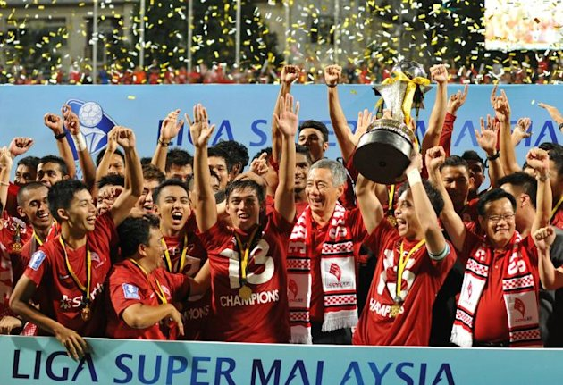 Singapore's Prime Minister Lee Hsien Loong celebrates with LionsXII players after they clinched the Malaysian Super League title in July last year, rekindling the city-state's glory days in the competition after a nearly two-decade absence (AFP)